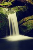 Cascade on small mountain stream. Cold crystal  water is falling over basalt mossy boulders into small pool. Stock Photos