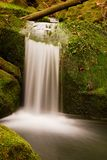 Cascade on small mountain stream. Cold crystal  water is falling over basalt mossy boulders into small pool. Stock Images
