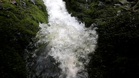 Cascade on small mountain stream, water is running trough big crack Stock Images