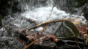 Cascade on small mountain stream, water is running. Trough big crack in basalt boulder and bubbles create on level milky water stock footage