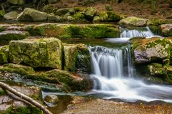 Cascade on a spring in Tatra mountains with rocks covered in moss. Smooth water fall royalty free stock photography