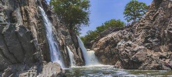 Cascade stupéfiante sur la roche brune dure dans une jungle de campagne dans un beau jour ensoleillé avec les arbres verts photo libre de droits