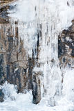 Cascade of water frozen in the vertical wall of the mountain. Icicles from ice on frozen on the mountain wall Stock Photo
