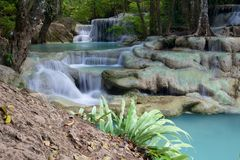 Cascade waterfall in Erawan. Beautiful waterfall cascade in Erawan National Park with green plant in foreground Royalty Free Stock Image