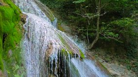 Cascade Waterfall Flowing Down On Mossy Rocks. CLOSE UP shot made at picturesque place showing spellbinding cascade waterfall flowing down on mossy rocks with stock video footage