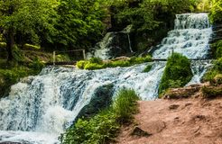 Cascade waterfall among forest locality by a bright sunny day. Cascade waterfall among forest locality. Waterfall Dzhuryn, Nyrkiv village, Ternopil region Royalty Free Stock Photo