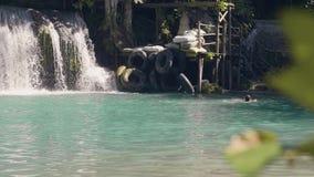 Cascade waterfall splashing in tropical waterfall and young woman swimming in fresh water. Beautiful tropical waterfall.  stock video footage