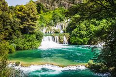 Cascade waterfalls in the forest flows into the turquoise lake. Krka, National Park, Dalmatia, Croatia stock images