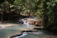 Cascades with clear water in National park Kuang Si Waterfall, L. Cascades with clear turquoise water and jungle around in National park Kuang Si Waterfall, Lao Royalty Free Stock Photos