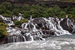 Cascades majestueuses avec les roches et l'herbe autour Photographie stock libre de droits