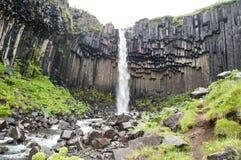 Cascades majestueuses avec les roches et l'herbe autour Images libres de droits