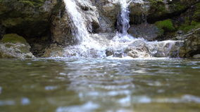 Cascades on small mountain river with rapids flowing in stony riverbed covered with moss. Pure fresh water in spring stock video footage