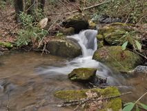 Cascades on Stone Mountain Creek in North Carolina. Water cascades over rocks creating small falls along Stone Mountain Creek in Stone Mountain State Park.  Low Stock Image