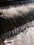 Cascades sur une rivière débordante Images stock