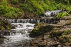 Cascades van het rollende water van de bergstroom op de rotsen stock afbeelding