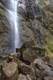 Cascading falls behind rocks. Royalty Free Stock Image