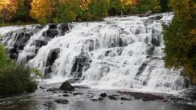 Cascading Lower Bond Falls Loop. Water cascades down the rock face of Bond Falls, a beautiful waterfall in Michigan's Upper Peninsula. Loops seamlessly stock footage