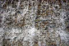 Cascading water. Water cascading over this rock wall royalty free stock photo