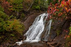 Autumn at Jacobs Falls in the Upper Peninsula of Michigan, USA. Cascading water flows rapidly over Jacob's Falls near Eagle River Michigan. Autumn colors and Royalty Free Stock Photography