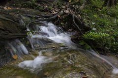 Cascading water stream at Kanching waterfall, located in Malaysia,wet and mossy rock, surrounded by green rain forest Royalty Free Stock Images