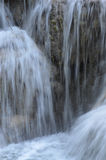 A cascading waterfall. Close-up of a waterfall onto brown rocks. The water is blurred Royalty Free Stock Image