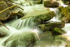 Cascading waterfall closeup very smooth water with wet rocks Stock Photo