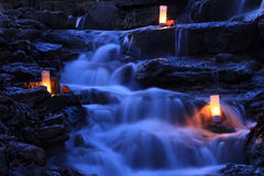 Cascading Waterfall Garden with Candles. Cascading waterfall garden at twilight with candles glowing on the rocks Royalty Free Stock Photography