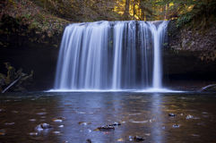 Cascading waterfall with light blue reflection in water. Stock Photos