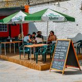 Sign with British humour at a pub in Cascais, Portugal. Cascais, Portugal - August 3rd, 2018: Sign with British humour at a pub on the promenade in Cascais royalty free stock image