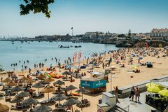 Crowded Duquesa beach on a hot summer`s day, with the town of Cascais in the background including the ancient fort. Cascais, Portugal - August 30th, 2018 stock photography