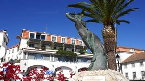 Pan up of a mermaid statue with white-washed buildings covered colourful flowers background, Cascais, Portugal. Cascais, Portugal - May 22, 2019: Pan up of a stock footage