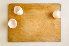 Cascas de ovo na placa de corte de madeira Fotos de Stock