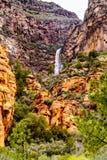 Cascata che scende le montagne variopinte dell'arenaria in canyon di Oak Creek lungo l'Arizona SR89A fra Sedona e l'albero per ba fotografie stock