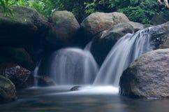 Cascata con la pietra di muschio verde in foresta pluviale, Kiriwong Vil immagine stock