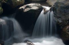 Cascata con la pietra di muschio verde in foresta pluviale, Kiriwong Vil fotografia stock