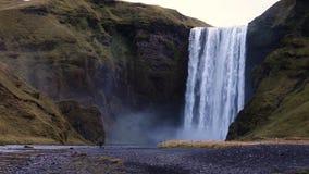 Cascata dell'Islanda sui precedenti delle montagne Le correnti di acqua cadono dalla scogliera e cadono stock footage