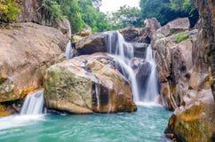 Cascata della giungla con acqua corrente, grandi rocce Fotografie Stock Libere da Diritti