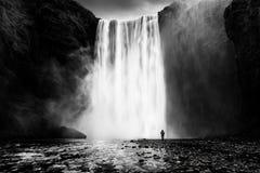 Cascata di Skogafoss con un uomo solo Fotografie Stock Libere da Diritti