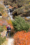 Cascata diritta della montagna di giovane viaggiatore con zaino e sacco a pelo felice della donna Immagine Stock Libera da Diritti