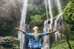 Cascata facente una pausa della donna con le sue mani sollevate fotografia stock