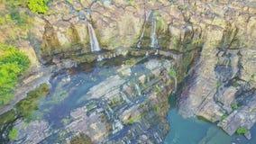 Cascata próxima da cachoeira da vista aérea das rochas na água azul filme