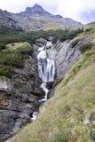 Cascata sotto la sommità di una strada Stelvio, Italia della montagna Immagine Stock Libera da Diritti