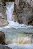 Cascate di una torrente montano che scorre fra i massi enormi immagine stock
