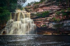 Poço do diabo waterfall, Mucugezinho river, Lençóis - Bahia, Brazil. Cascate shot a slow shutter speed. River with dark waters and there are tourists on stock photo