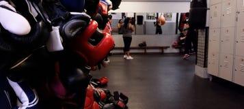 Caschi e guanti di pugilato che appendono sulla parete laterale contro il contesto dei pugili di addestramento Fotografia Stock