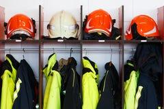 Caschi e vestiti del fuoco disposti in suo armadio Fotografia Stock