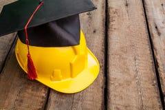 Casco amarillo con el sombrero del estudiante en de madera Fotos de archivo
