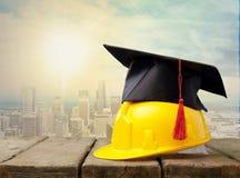 Casco amarillo con el sombrero del estudiante en de madera Fotografía de archivo