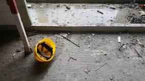 Casco amarillo del casco de seguridad en el piso sucio Imagen de archivo libre de regalías