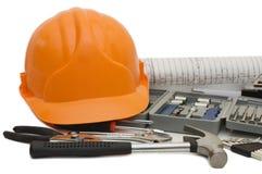 Casco anaranjado y diversas herramientas Imagen de archivo libre de regalías